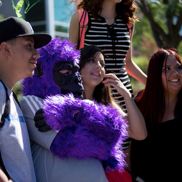 students posing with purple ape at block party