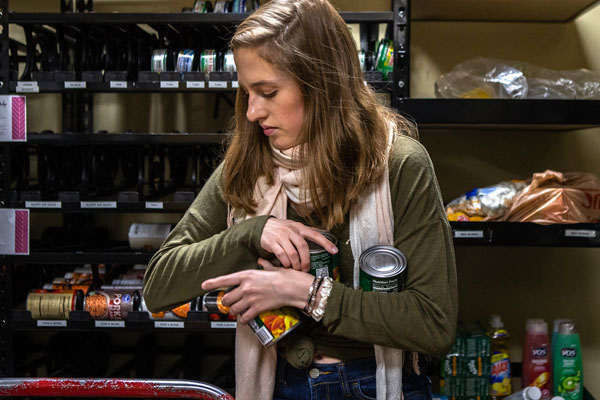 student holding cans of food